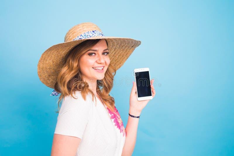 Gelukkige glimlachende vrouw die celtelefoon met het zwarte scherm op een blauwe achtergrond tonen royalty-vrije stock afbeelding
