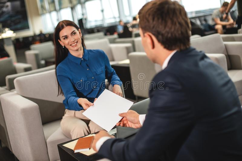 Gelukkige glimlachende vrouw die document bereiken aan zakenman stock foto's