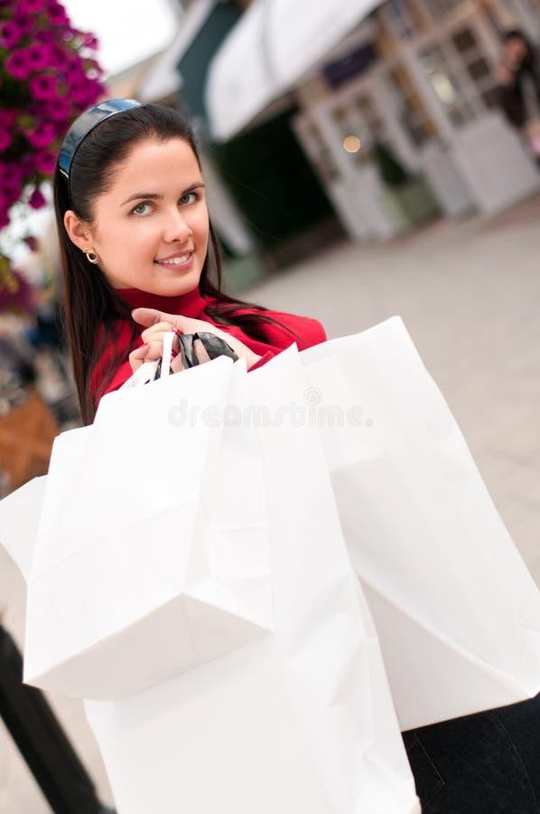 Gelukkige glimlachende vrouw die met witte zakken winkelen stock fotografie