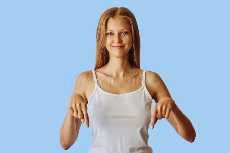 Gelukkige glimlachende vrouw die neer met wijsvingers richten royalty-vrije stock afbeeldingen