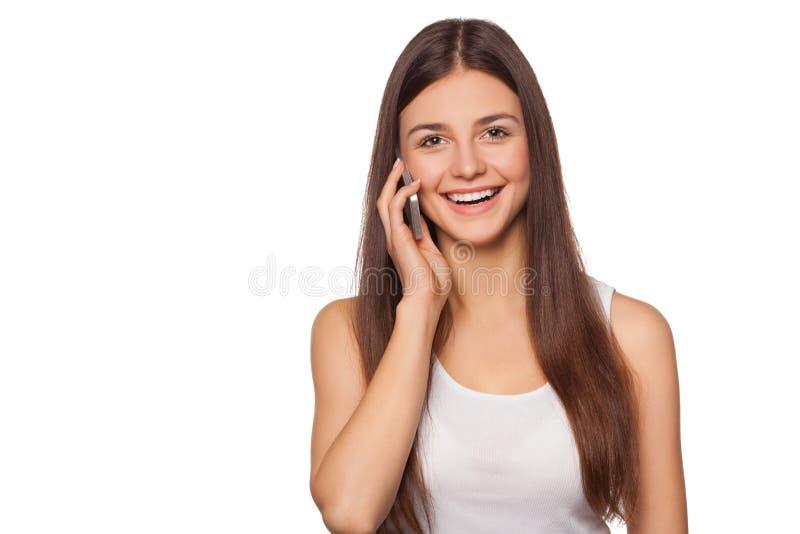 Gelukkige glimlachende vrouw die op mobiele die telefoon spreken, op witte achtergrond wordt geïsoleerd Mooi meisje met een smart stock afbeeldingen
