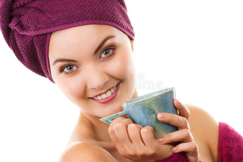 Gelukkige glimlachende vrouw die in purpere badjas, van versheid en welzijn genieten stock foto