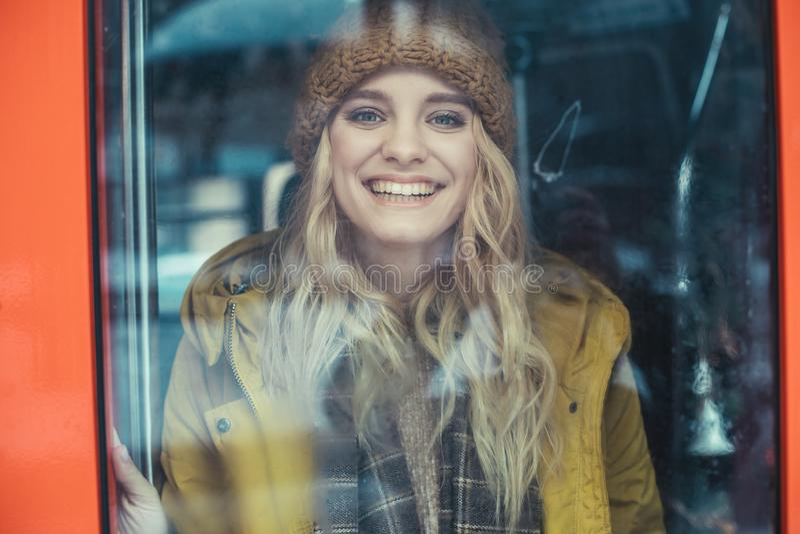 Gelukkige glimlachende vrouw die van busvenster kijken stock foto