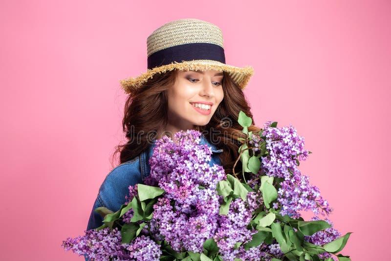 Gelukkige glimlachende vrouw die van geur van boeket lilac bloemen genieten over kleurrijke blauwe achtergrond royalty-vrije stock afbeelding