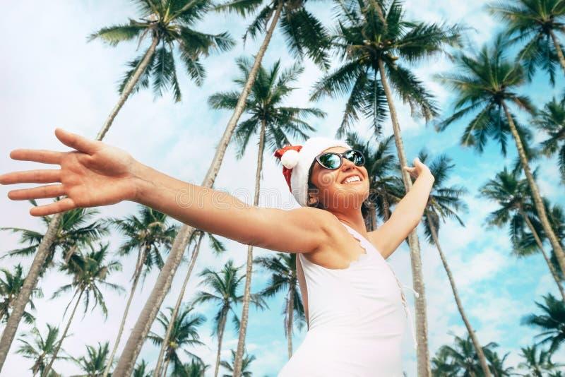 Gelukkige glimlachende vrouw in het verblijf van de Kerstmanhoed onder palmen Christma stock fotografie