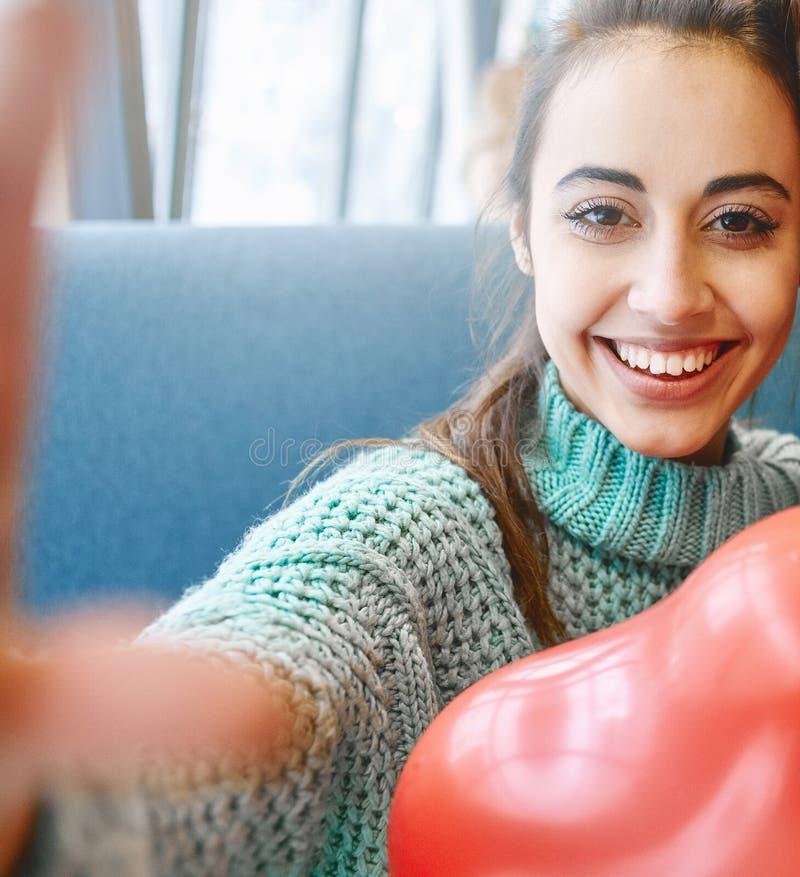 Gelukkige glimlachende vrouw in liefde die selfie in Valentijnskaartendag maken royalty-vrije stock foto's