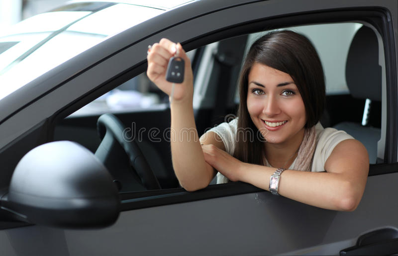 Gelukkige glimlachende vrouw met autosleutel stock fotografie