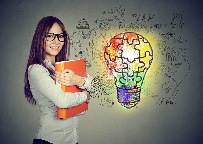 Gelukkige glimlachende vrouw met oranje omslagnotitieboekje dichtbij een concrete muur met een heldere van de bedrijfs raadsel gl stock afbeelding