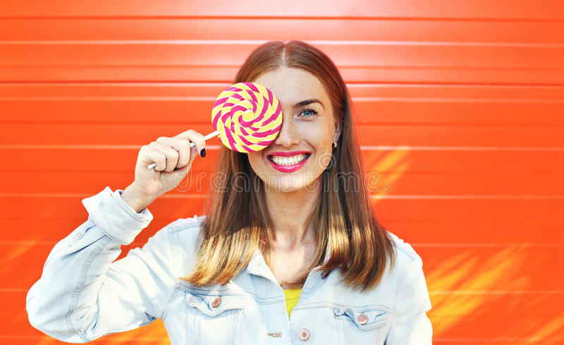 gelukkige glimlachende vrouw met zoete karamellolly over kleurrijke oranje achtergrond stock fotografie