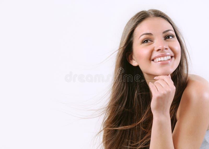 Gelukkige glimlachende vrouw met zuivere huid en winderig helder haar stock afbeelding