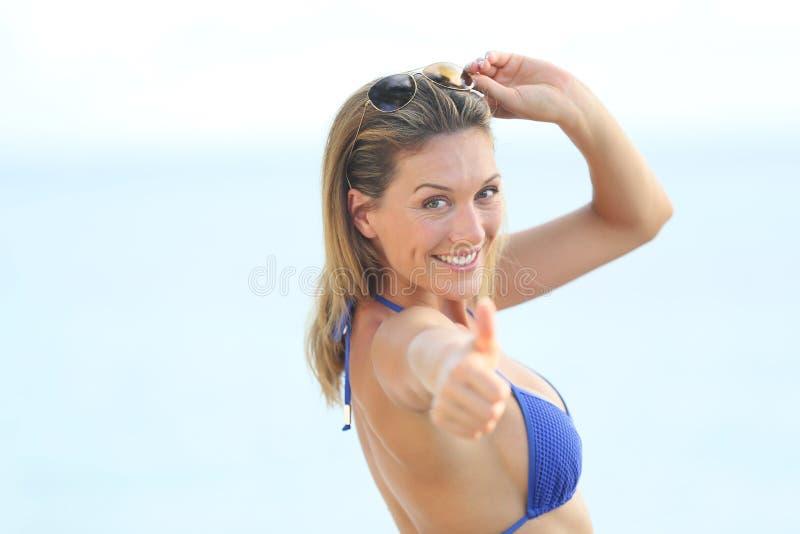 Gelukkige glimlachende vrouw op het strand met een omhoog duim stock fotografie