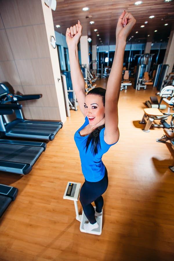 Gelukkige glimlachende vrouw op schalen bij de gymnastiek stock afbeeldingen
