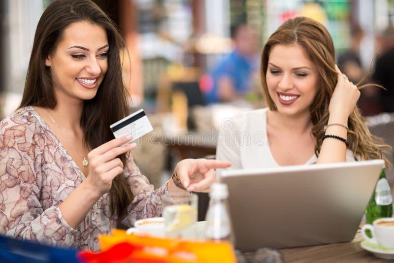 Gelukkige glimlachende vrouwelijke vrienden die online shooping royalty-vrije stock afbeeldingen