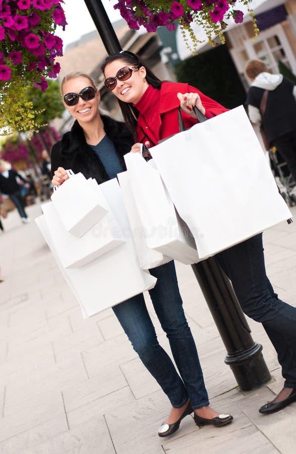 Gelukkige glimlachende vrouwen die met witte zakken winkelen royalty-vrije stock foto