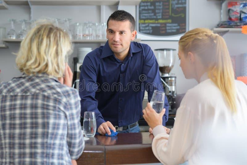 Gelukkige glimlachende vrouwen die zich bij bar bevinden en met barman flirten stock afbeeldingen
