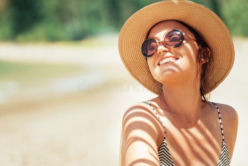 Gelukkige glimlachende zon buthing vrouw in het portret van de strohoed Palmschaduwen op het lichaam Gezondheid het looien concep stock foto's