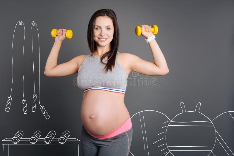 Gelukkige glimlachende zwangere vrouw die sportoefeningen doen royalty-vrije stock foto's