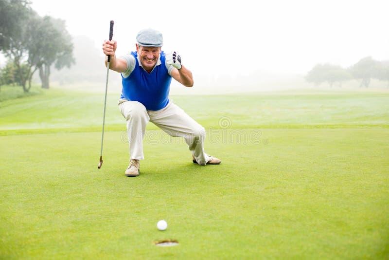Gelukkige golfspeler die bij groen zetten toejuichen royalty-vrije stock foto's
