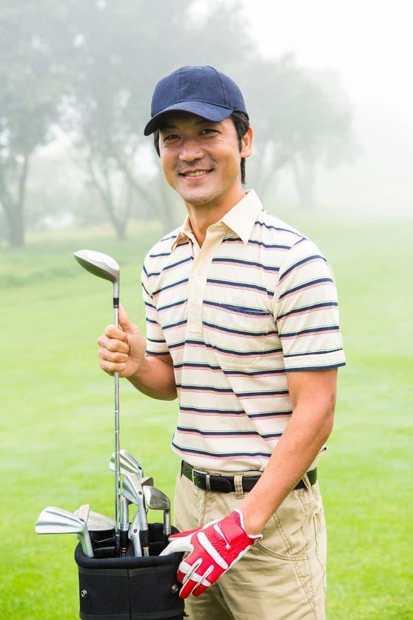 Gelukkige golfspeler die club van golfzak nemen stock afbeelding