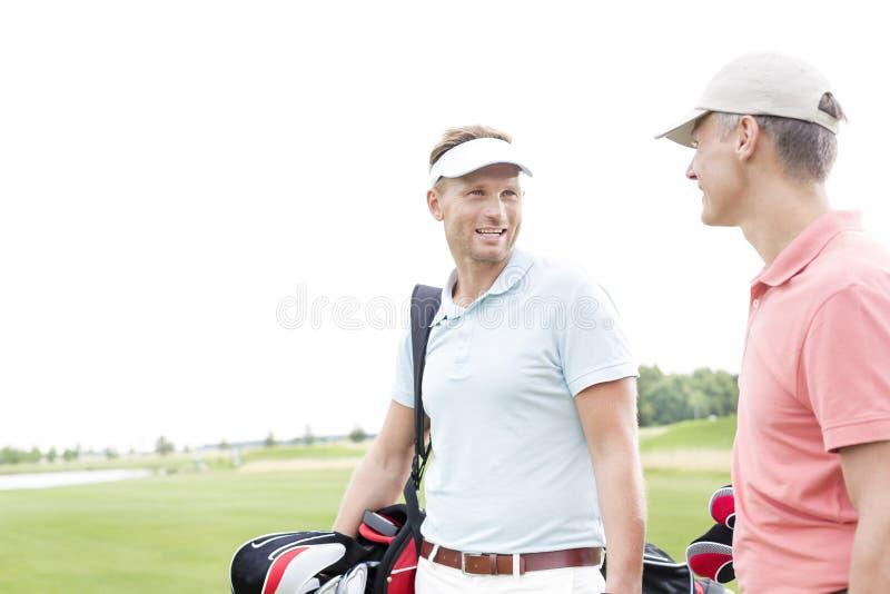 Gelukkige golfspeler die met mannelijke vriend tegen duidelijke hemel communiceren royalty-vrije stock fotografie