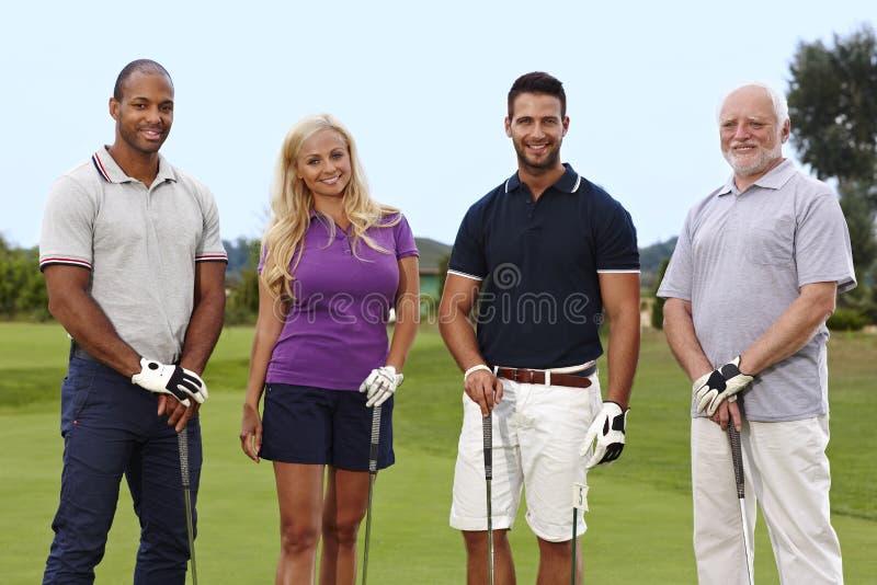 Gelukkige golfspelers op green stock afbeelding