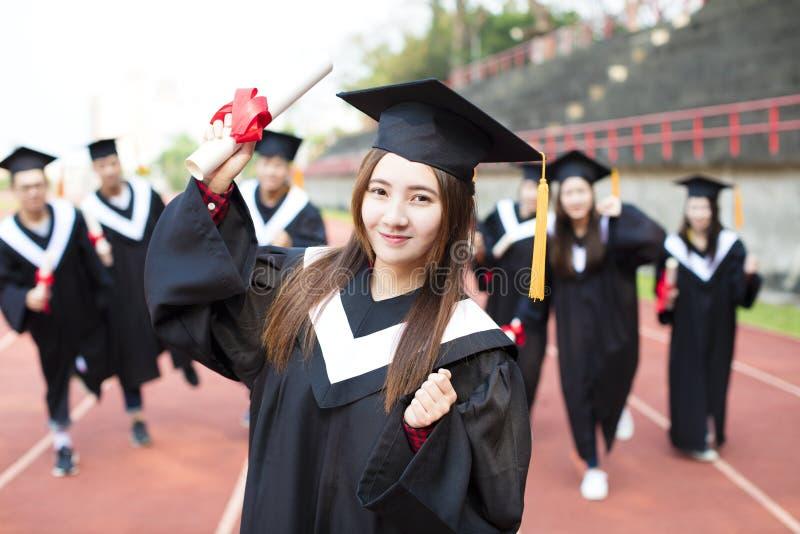 Gelukkige graduatiestudenten met diploma's in openlucht stock afbeeldingen