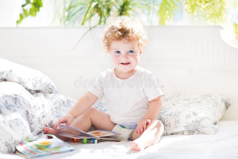 Gelukkige grappige baby die een boek in haar oudersbed lezen stock afbeeldingen