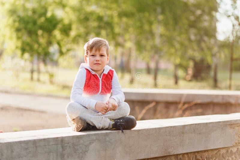 Gelukkige grappige jongen van zes jaar oud in de zomer in openlucht stock afbeelding