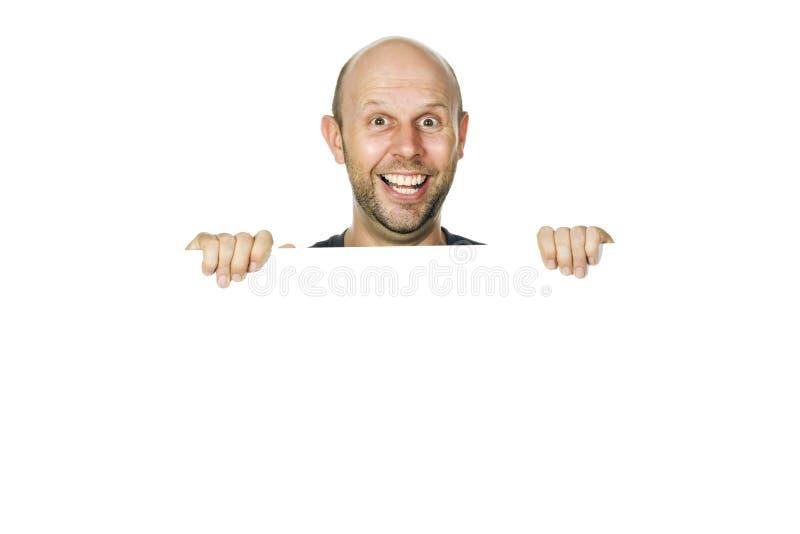 Gelukkige grappige mens die over een muur of een wit teken gluurt. royalty-vrije stock foto's