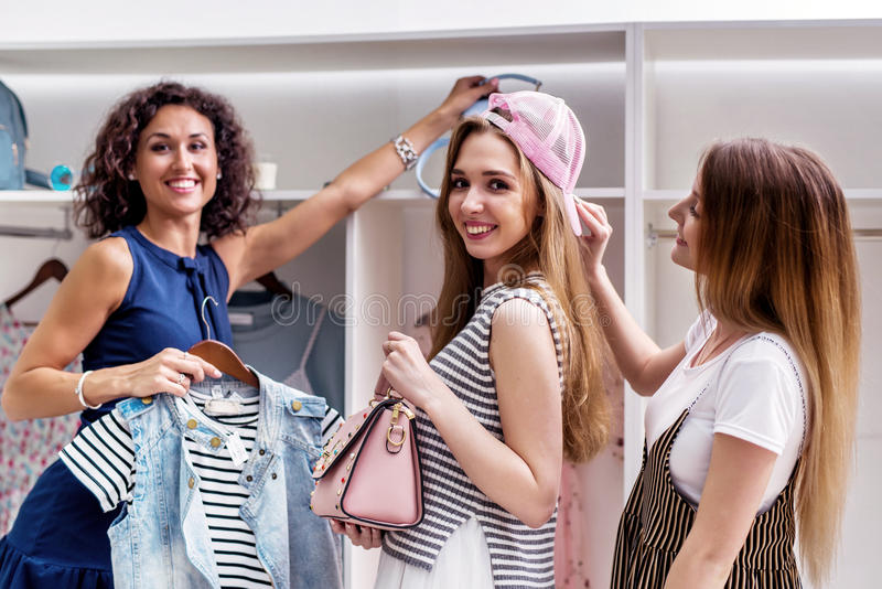 Gelukkige grappige vrouwelijke vrienden nieuwe kleren plukken en toebehoren die camera in boutique bekijken stock foto