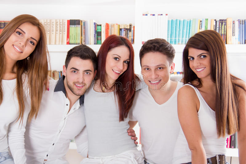 Gelukkige groep en vrienden die thuis glimlachen koesteren stock afbeeldingen