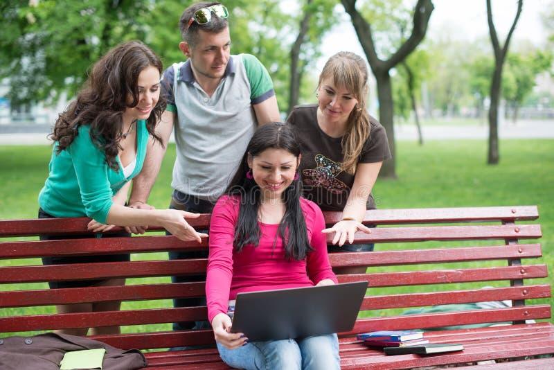 Gelukkige groep het jonge studenten zitten stock afbeelding