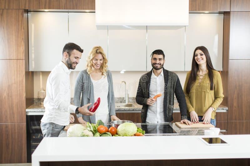 Gelukkige groep jonge mannen en vrouwen in moderne keuken royalty-vrije stock afbeelding
