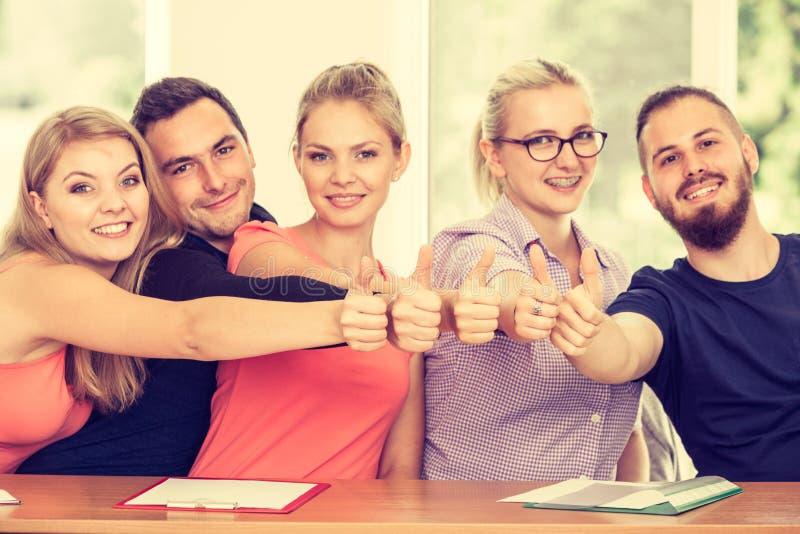 Gelukkige groep studenten met omhoog duimen stock fotografie