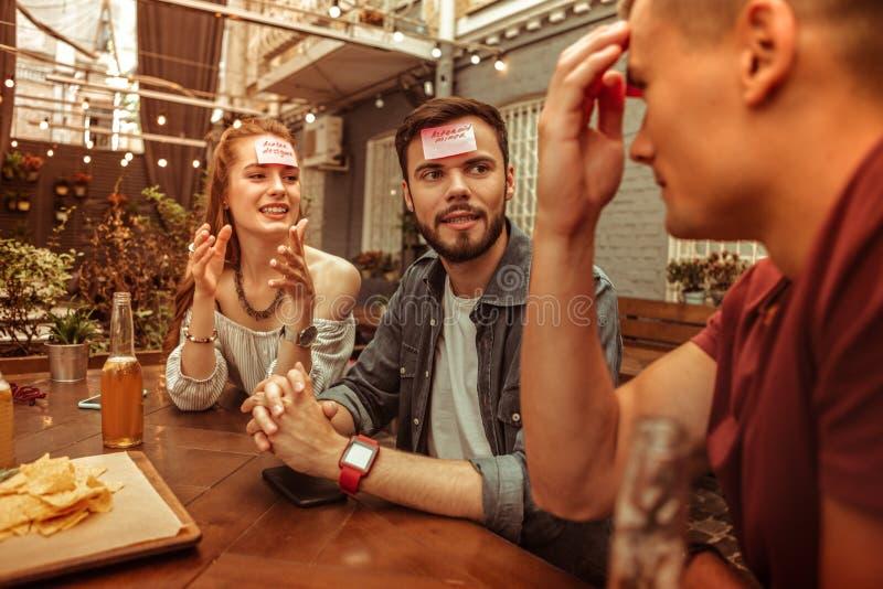 Gelukkige groep vrienden die hedbanz spel spelen bij de bar royalty-vrije stock afbeeldingen