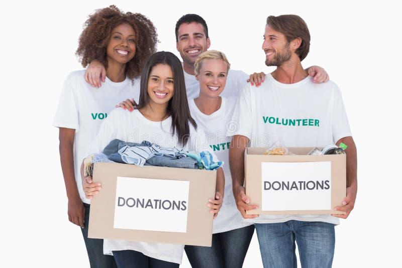 Gelukkige groep vrijwilligers die de dozen van de klerenschenking houden stock fotografie