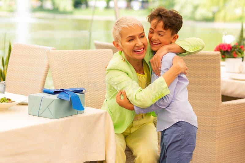 Gelukkige grootmoeder die haar knappe donker-haired jongen koesteren stock foto's