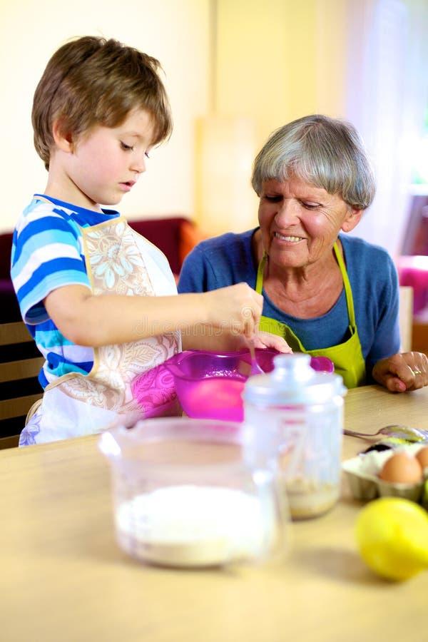 Gelukkige grootmoeder die kleinzoon kokende cake helpt stock fotografie