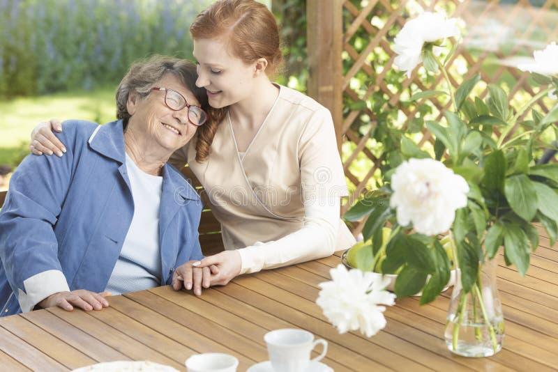 Gelukkige grootmoeder die van tijd met vriendschappelijke verpleegster op terra genieten royalty-vrije stock afbeelding