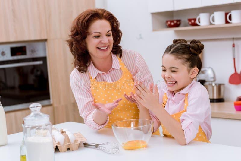 gelukkige grootmoeder met weinig kleindochter die deeg voor het koken voorbereiden royalty-vrije stock afbeeldingen
