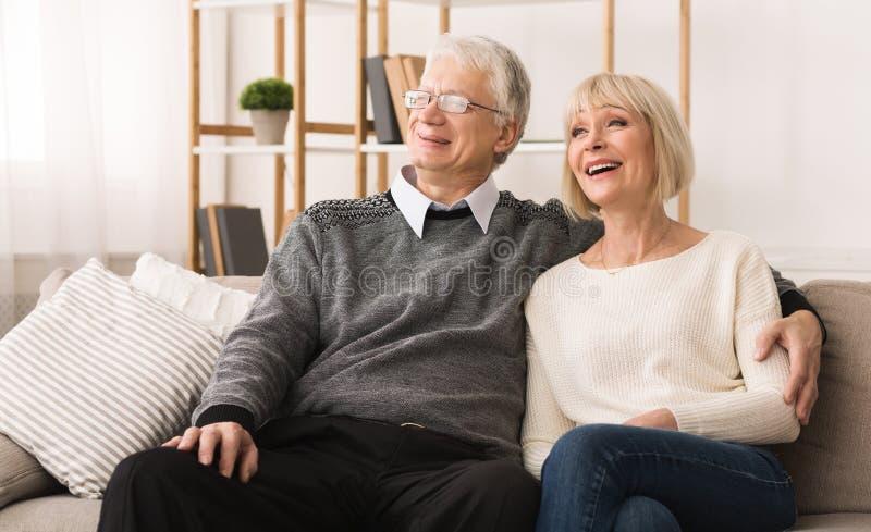 Gelukkige grootouders die rust hebben, die op bank zitten royalty-vrije stock foto
