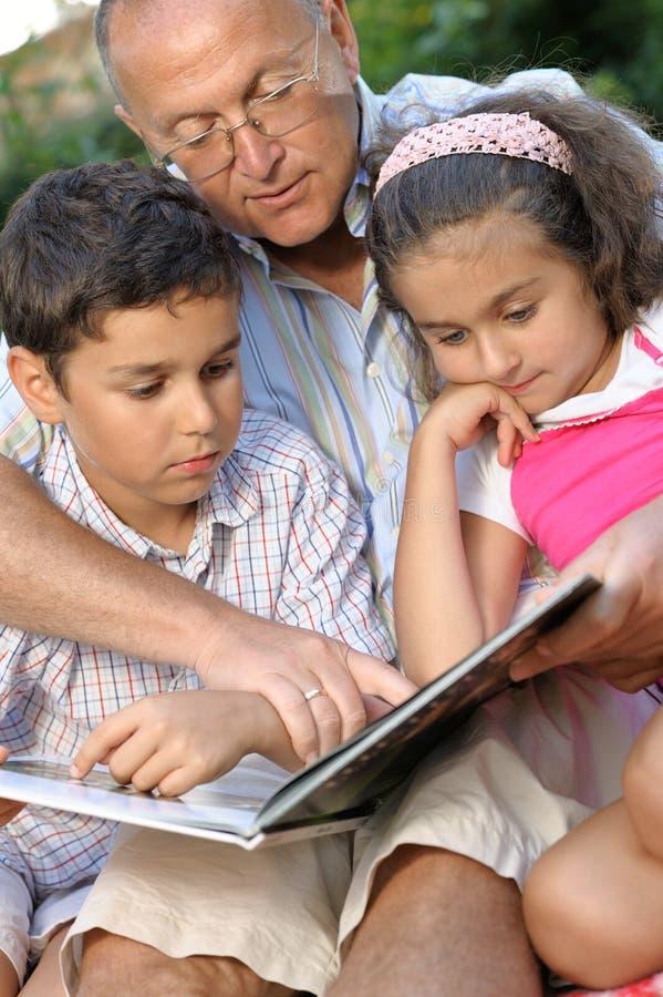 Gelukkige grootvader en jonge geitjes die boek lezen royalty-vrije stock foto
