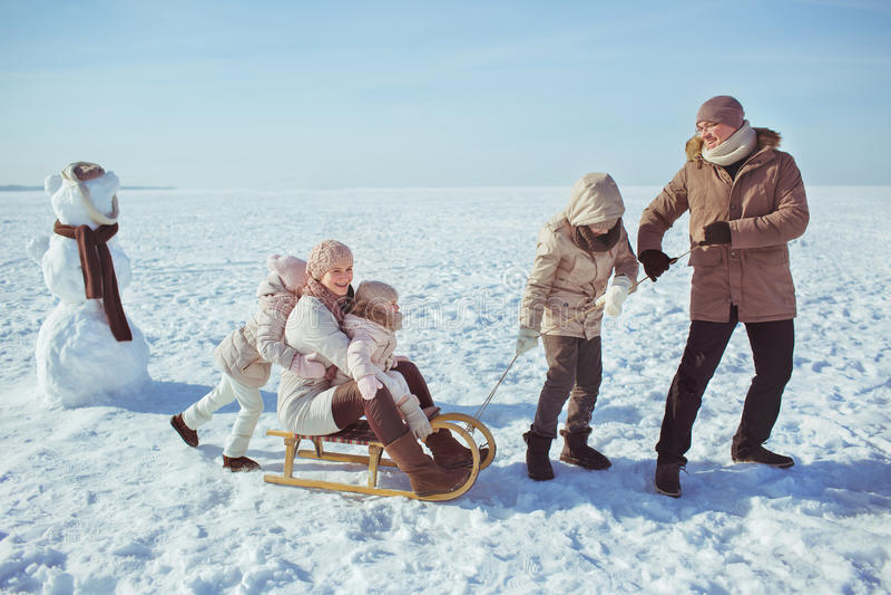 Gelukkige grote familieslee dichtbij een sneeuwman in de winter stock fotografie