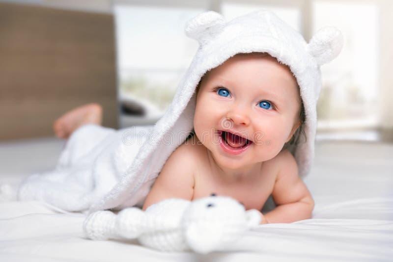 Gelukkige halfjaarlijkse oude baby die op een bed liggen royalty-vrije stock fotografie