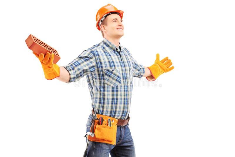 Gelukkige handarbeider die een baksteen houden en wapens uitspreiden royalty-vrije stock afbeelding