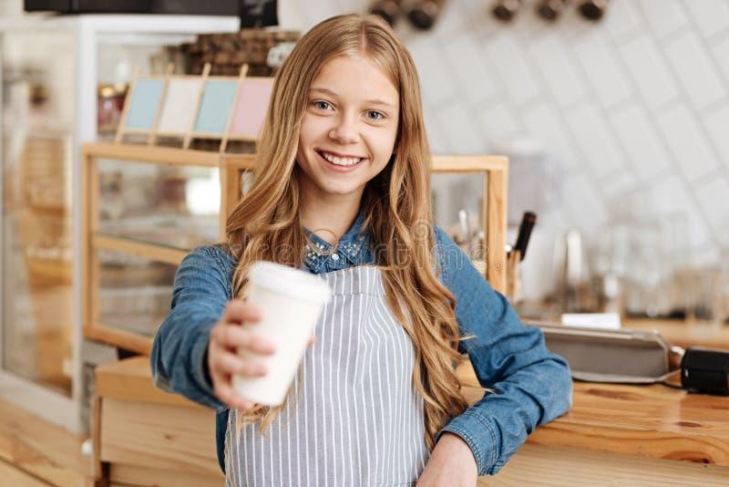 Gelukkige het charmeren barista die een kop van koffie overhandigen royalty-vrije stock foto