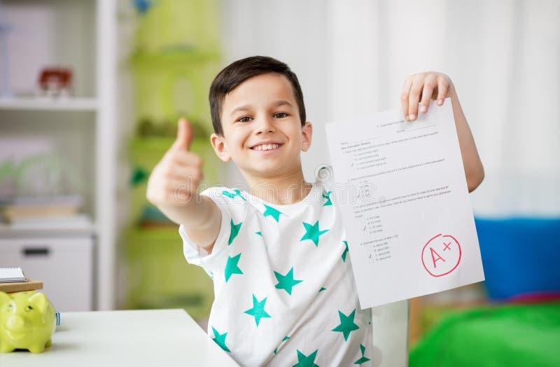 Gelukkige het glimlachen de schooltest van de jongensholding met een rang royalty-vrije stock foto's