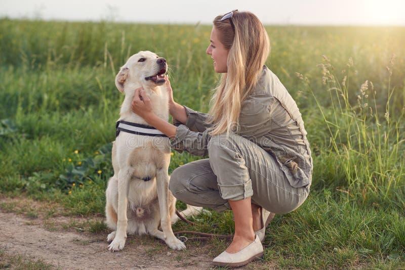 Gelukkige het glimlachen gouden hond die een het lopen uitrustingszitting dragen die zijn vrij jonge vrouw onder ogen zien owne royalty-vrije stock afbeelding