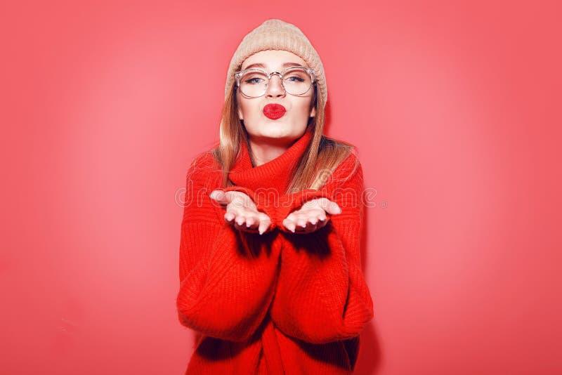 Gelukkige het Glimlachen Hipster Meisjeskus in gebreide rode sweater en hoed die pret hebben Leuk meisje in glusses met het doord royalty-vrije stock afbeelding