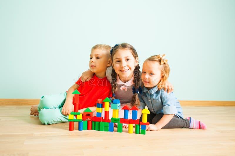 Gelukkige het glimlachen jonge geitjes achter het houten blokkenkasteel royalty-vrije stock foto